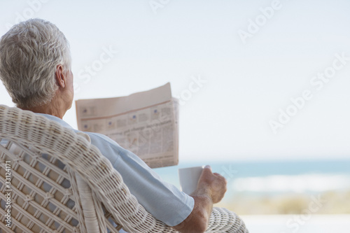 Senior man with coffee and newspaper on beach patio