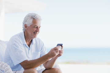 Senior man using cell phone on beach patio