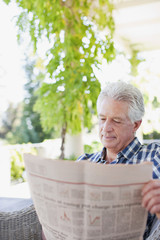 Senior man reading newspaper on patio