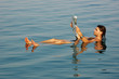 Man floating in a dead sea with newspaper