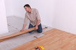 Man renovating the floor with wood panels
