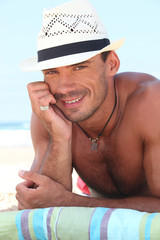 Muscular man in a straw hat lying on the beach