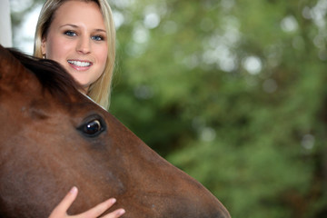 young blonde woman caressing a horse head