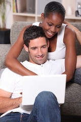 black woman is cuddling her boyfriend and doing computer