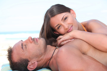 Couple in love sunbathing on the beach