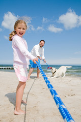 Tug-of-war - family with dog playing on the beach