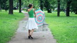 Young happy woman rotates in the park with umbrella, slow motion