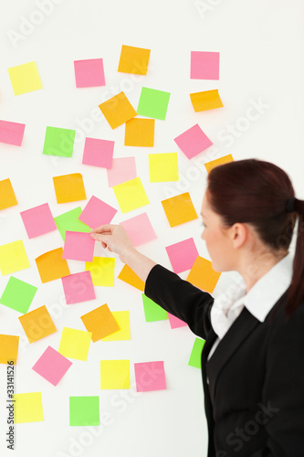 Woman putting colourful repositionable notes on a white wall