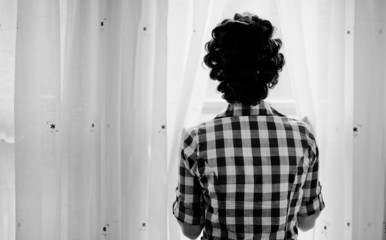 Girl looking through the window curtains