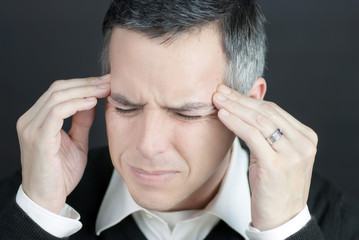 Man With Migraine Holds Temples