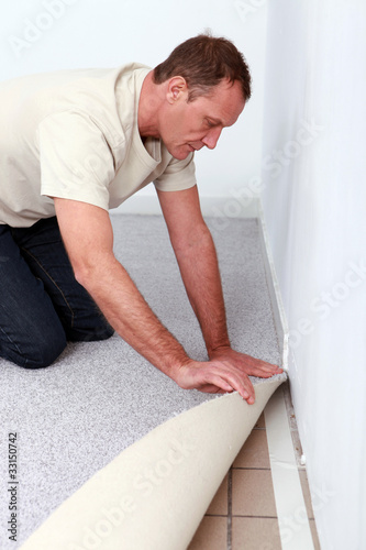 handyman is laying fitted carpet