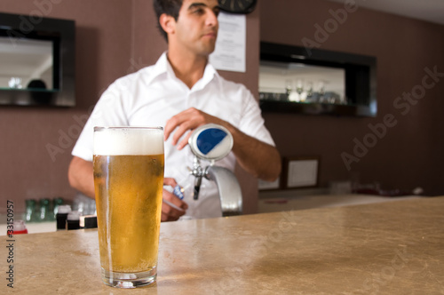 Bartender pouring beer from tap.