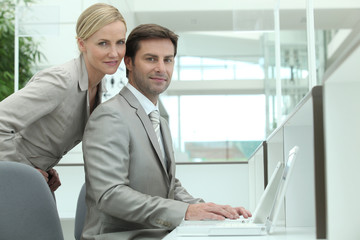 Business couple using a laptop computer