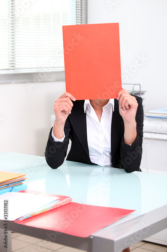 Smart woman hiding behind folder