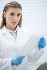 Woman in lab coat with surgical gloves