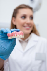 Dentist's assistant holding false teeth