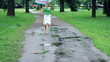 Woman colorful umbrella jumping over the puddles, slow motion