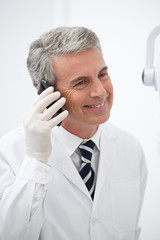 Smiling man in lab coat on the phone