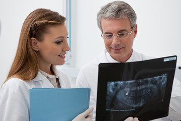 Dentist and assistant with x-ray and folder