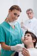 Dentist's assistant giving boy in chair beaker