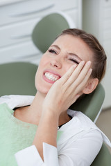 Woman having toothaches in dentist's chair