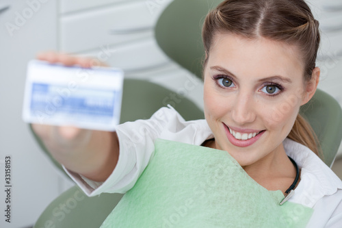 Woman in dentist's chair holding health insurance card