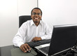Happy african american businessman working at desk smiling