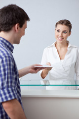 Receptionist passing document to man