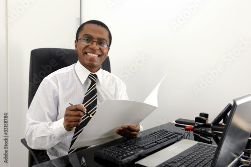 Happy business man or accountant reading documents at desk