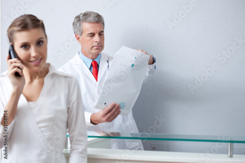 Assistant on the phone at the doctor's office with doctor holding envelope