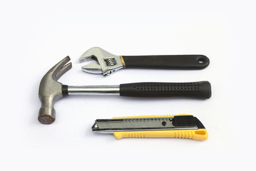 Wrench, pliers, a hammer, a white background.