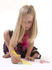 Little blonde girl drawing with crayon on white background.