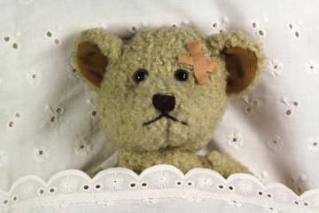 Teddy mit Pflaster im Bett