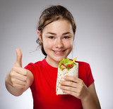 Girl eating big sandwich, showing Ok sign