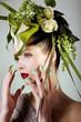 Beauty Frau mit grünem Kopfschmuck blickt fern
