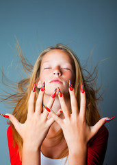 blonde girl with fashionable design of nails on dark blue