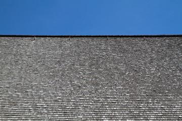 Verwittertes Holzschindeldach mit blauem Himmel