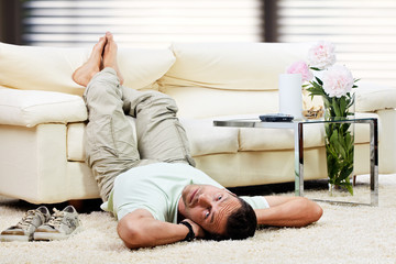 man relaxing in the living room, feet up