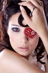 Frau mit rotem Schmuck Herz auf Auge scharf blickend close up
