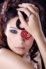 Frau mit rotem Schmuck Herz auf Auge cool blickend close up