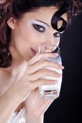 Hübsche Frau trinkt lächelnd Milch, hoch