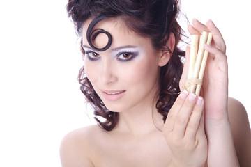 Hübsche Frau mit Löckchen und Stäbchen blickt verspielt, quer