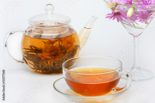 teapot, a cup of tea and a vase of flowers