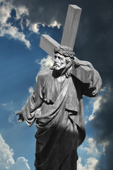 Jesus Christ carries the cross on the background of dramatic clo