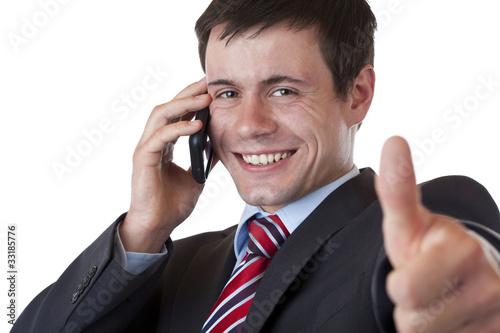 Leinwandbild Motiv Junger Geschäftsmann telefoniert und zeigt Daumen nach oben