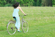 woman in blue dress riding an old bike  in green nature