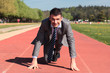young businessman on running track in summer
