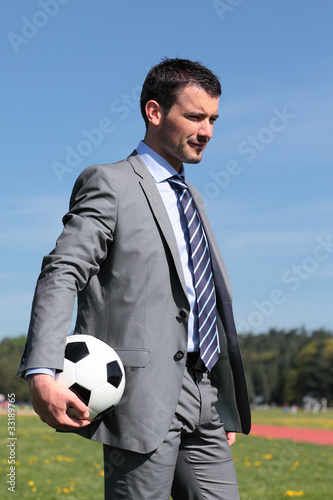 businessman with ball in a park in summer