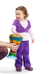 Little girl in violet beats with hand on djembe