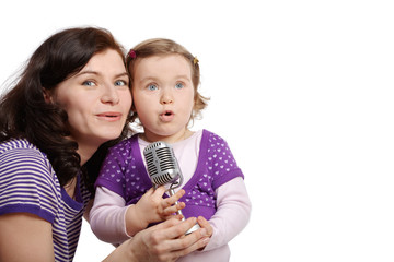 Mother with little daughter cheek to cheek sing into microphone.